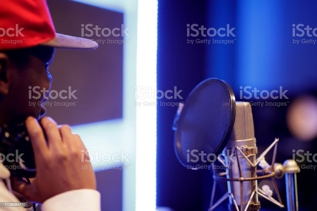 Rear view of black musician in music studio, focus on microphone,...