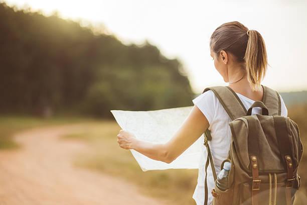 rear view of blonde girl looking at locatig map - geführtes lesen stock-fotos und bilder