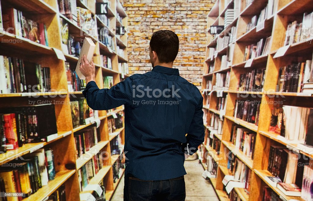 Rear view of bookseller in book store stock photo