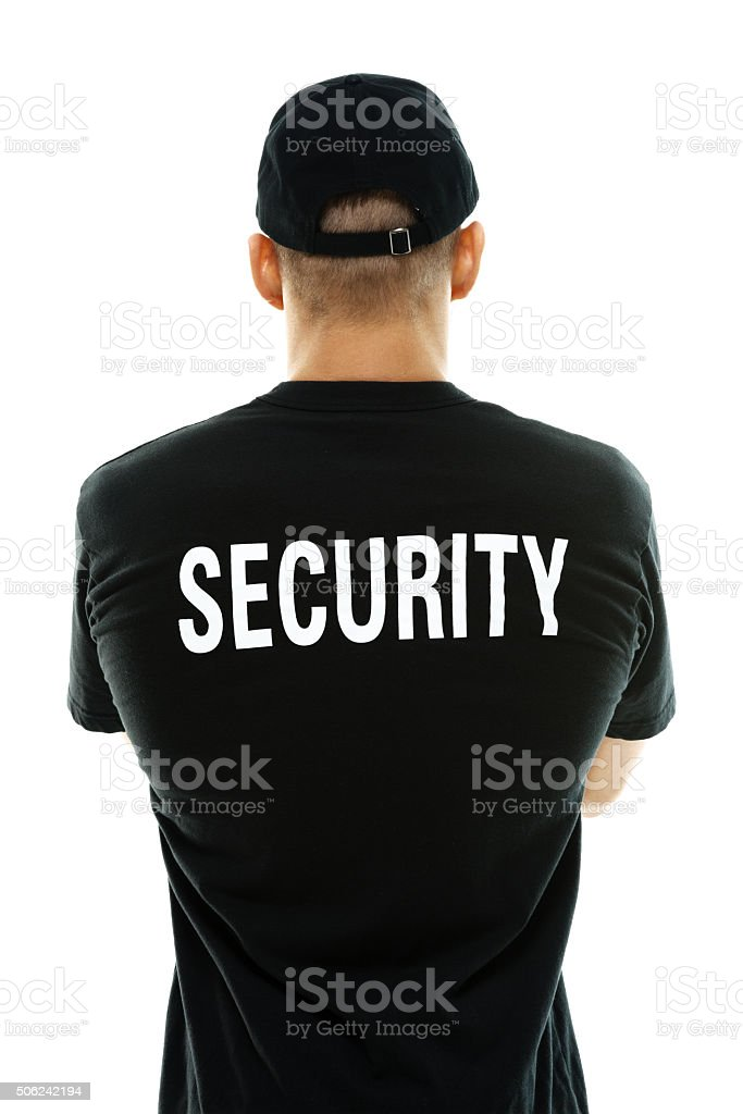 Rear view of bouncer standing with arms crossed stock photo