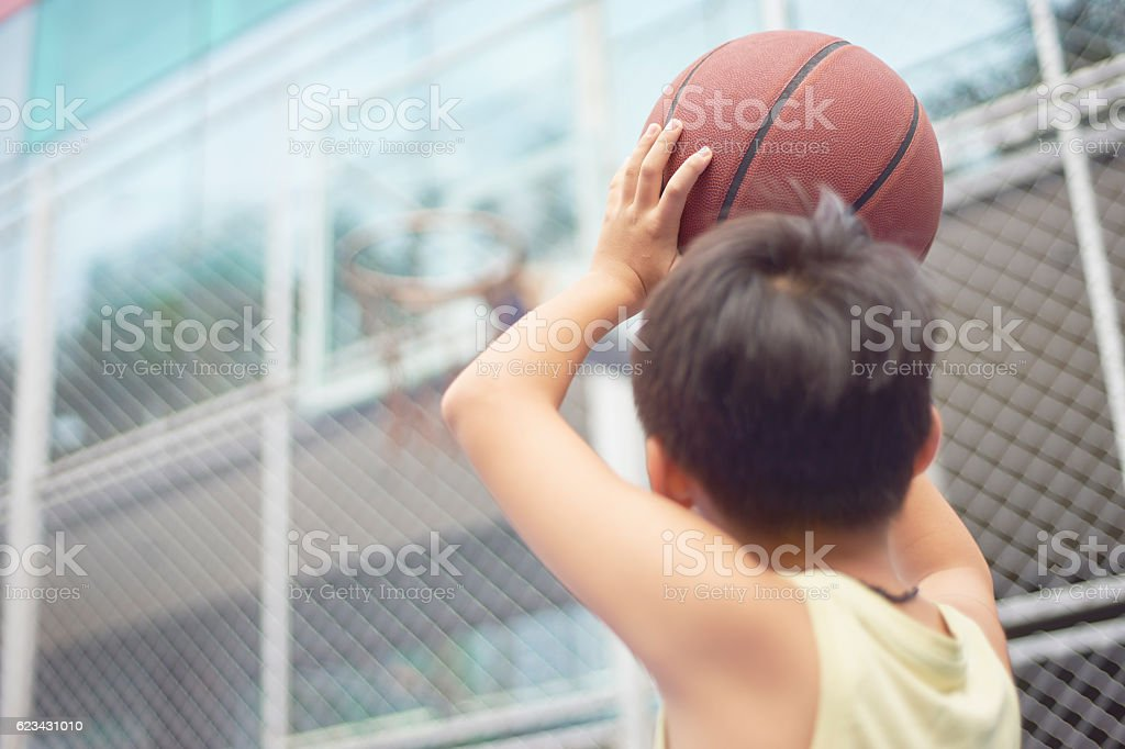 rear view of boy aiming basketball hoop before shooting stock photo
