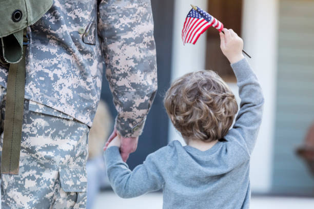 Rear view of boy holding hands with military dad stock photo