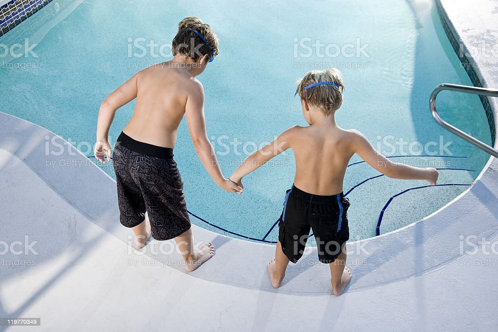Rear view of boys looking in swimming pool royalty-free stock photo