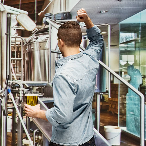 Rear view of brewmaster cheering in brewery stock photo