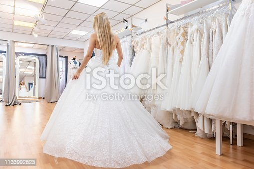 Rear view of blonde bride in bridal shop in haute couture wedding dress.