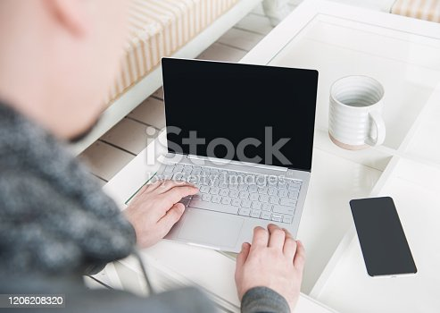 1151920695 istock photo Rear view of business man using laptop at home. Freelance or study concept 1206208320