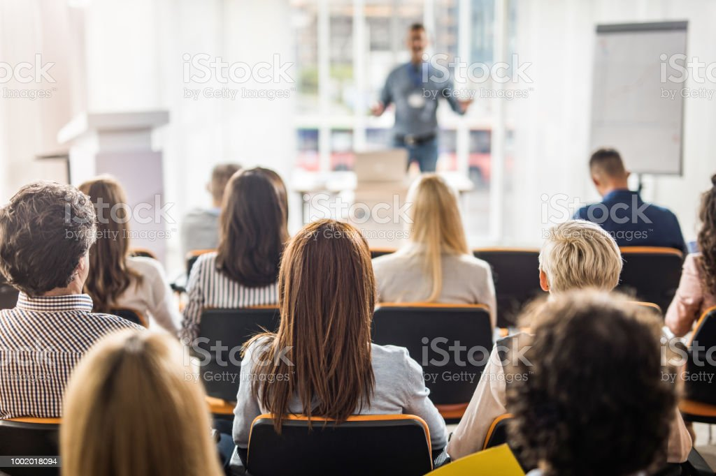 Rear view of business people attending a seminar in board room. Back view of large group of business people having a training class in a board room. Adult Stock Photo