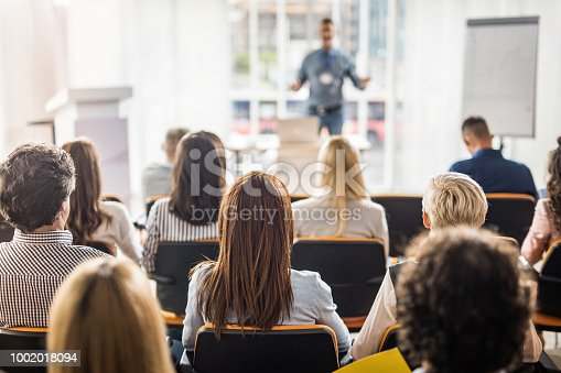 istock Rear view of business people attending a seminar in board room. 1002018094