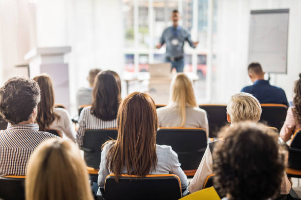 Rear view of business people attending a seminar in board room. stock photo