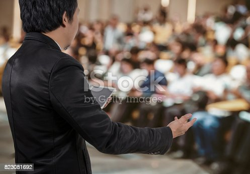 821463698 istock photo Rear view of Business People Conference Speaker on over the Abstract blurred photo of conference hall or seminar room with attendee background, business seminar and education concept 823081692