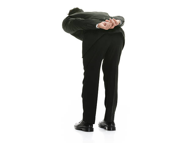 Rear view of businessman bowing stock photo