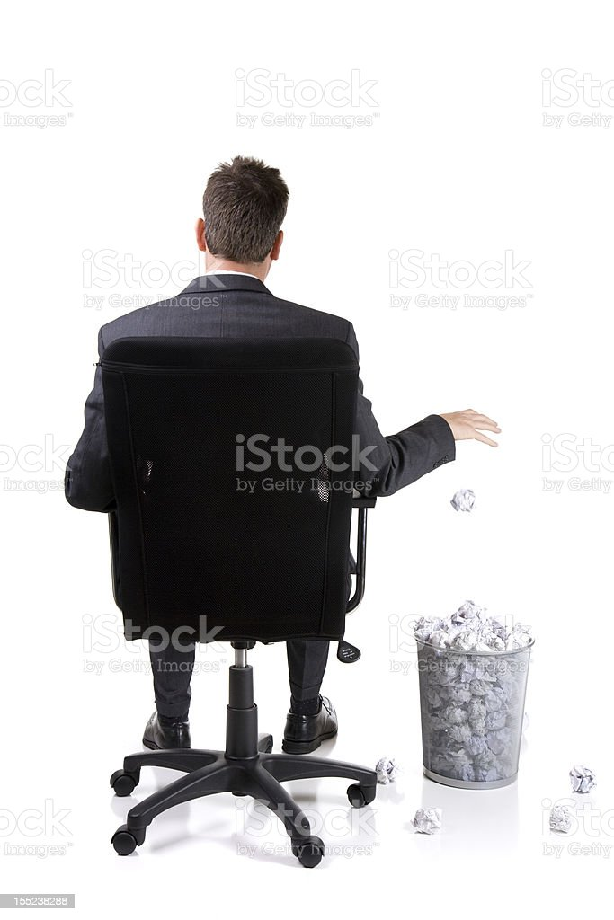 Rear view of businessman in chair with full waste paper bin stock photo