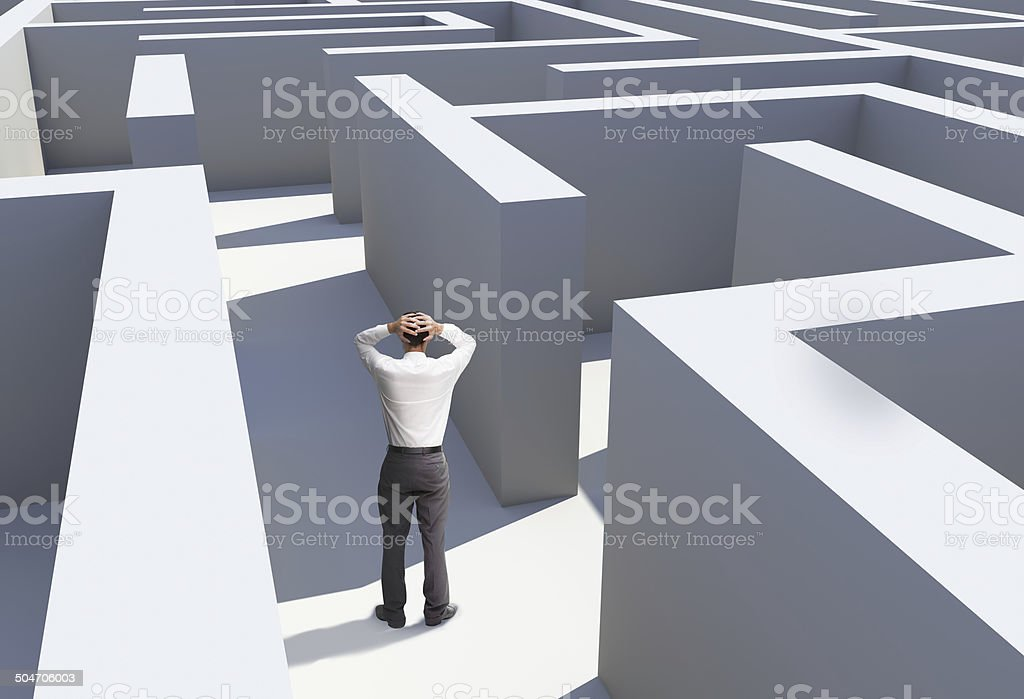 Rear view of businessman standing in maze stock photo