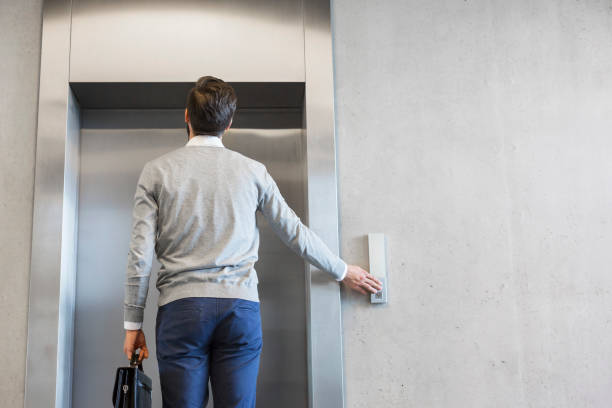 Rear view of businessman waiting for elevator at office stock photo