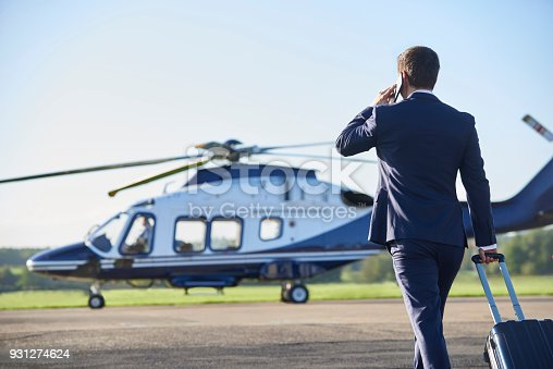 istock Rear View Of Businessman Walking Towards Helicopter Whilst Talking On Mobile Phone 931274624