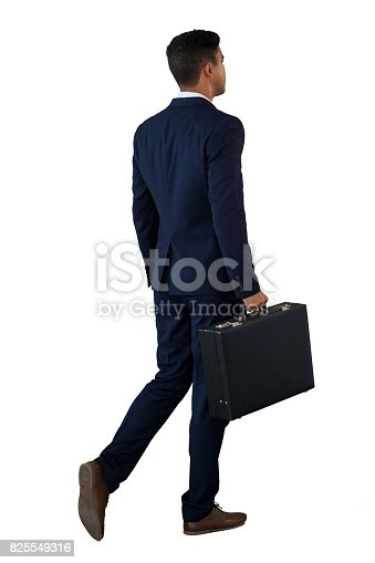 istock Rear view of businessman walking with briefcase 825549316