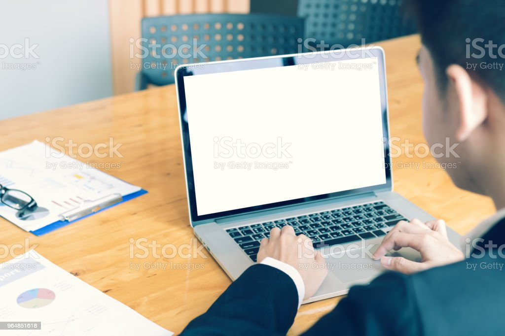Rear view of businessman working on desk at room office with laptop blank screen. royalty-free stock photo