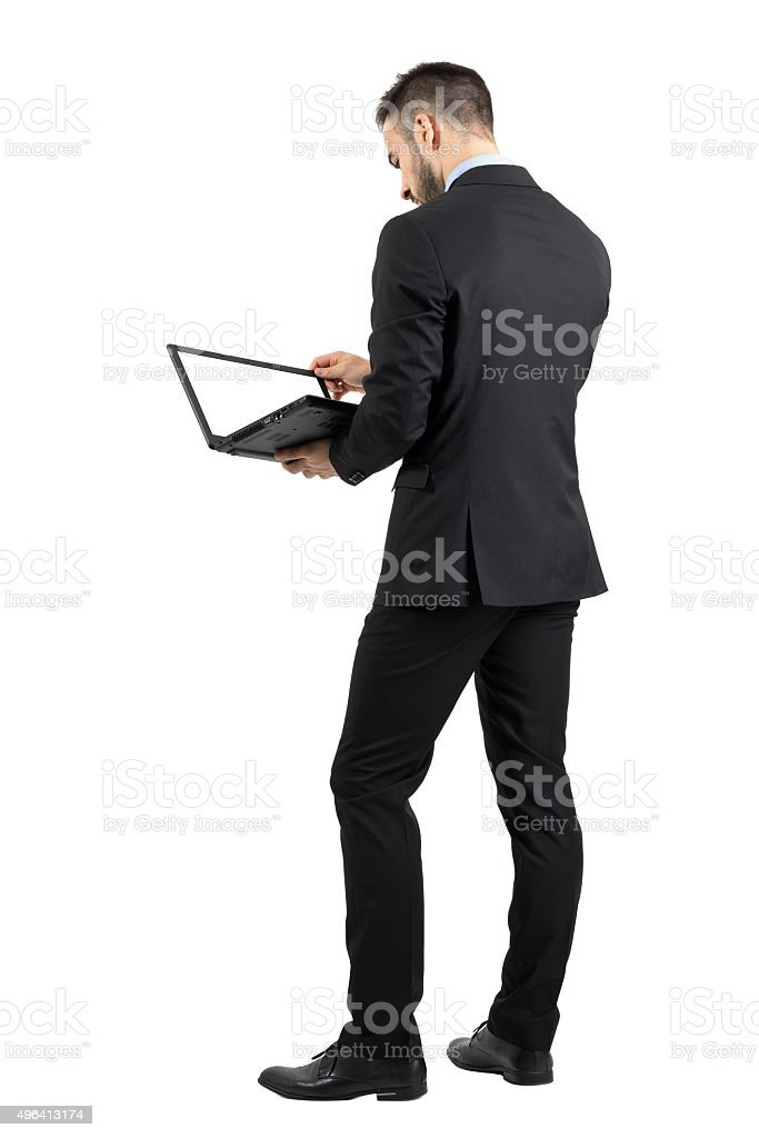 Rear view of businessman working on laptop with blank screen stock photo