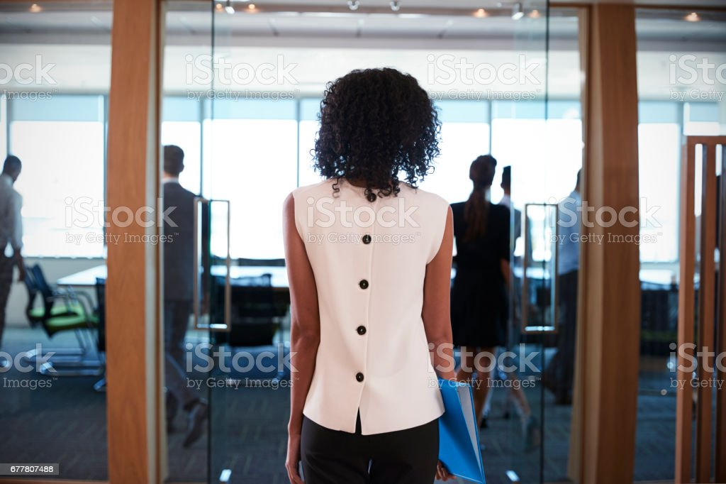 Rear View Of Businesswoman Entering Boardroom For Meeting stock photo
