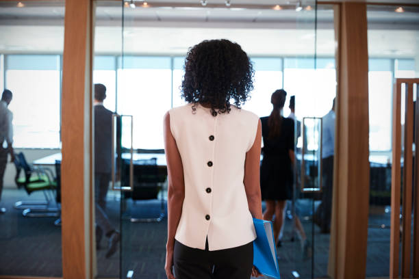 Rear View Of Businesswoman Entering Boardroom For Meeting Rear View Of Businesswoman Entering Boardroom For Meeting entering stock pictures, royalty-free photos & images