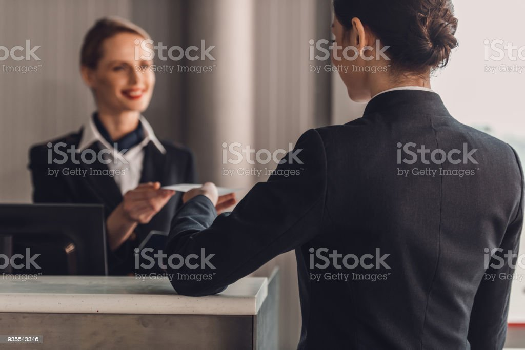 rear view of businesswoman giving ticket to staff at airport check in counter stock photo