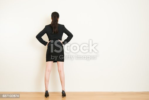 istock Rear view of businesswoman looking at on wall 637102874