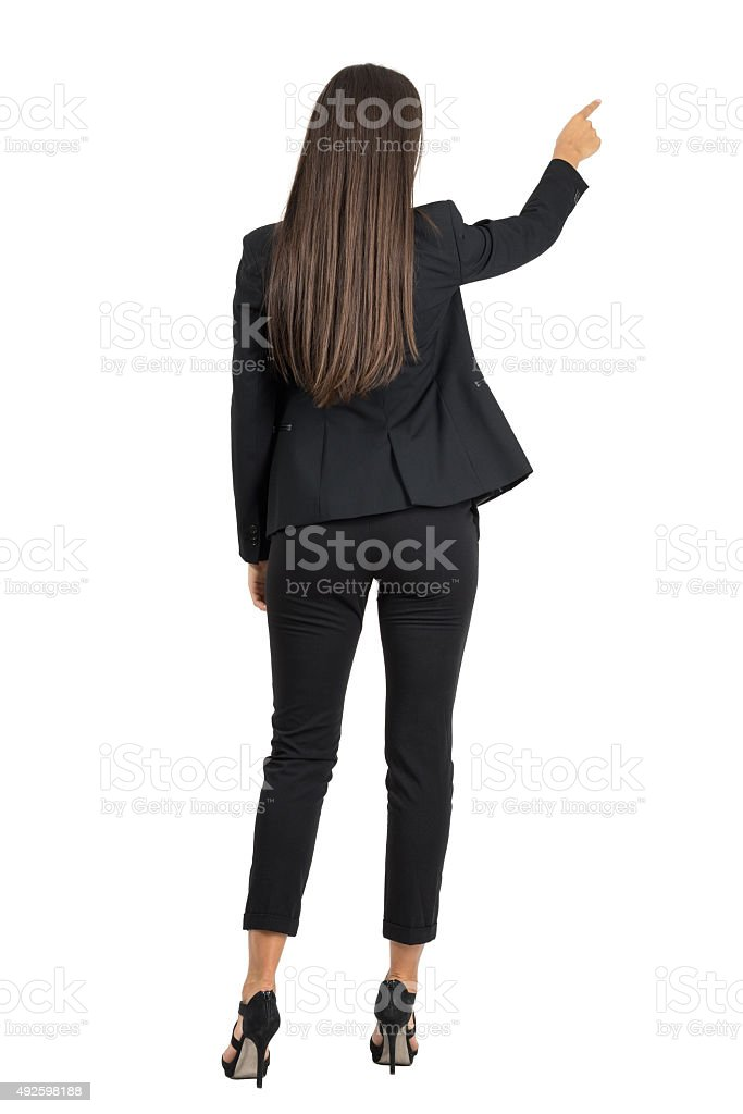 Rear view of businesswoman pointing on her right side stock photo