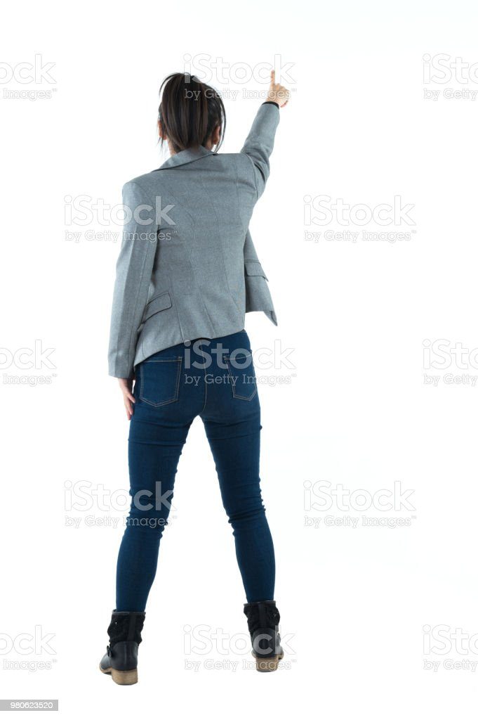 Rear view of businesswoman pointing up stock photo