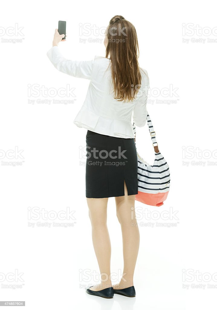 Rear view of businesswoman taking a selfie stock photo