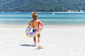 Back view of little boy with swimming tube running towards the sea in summer day. Copy space.
