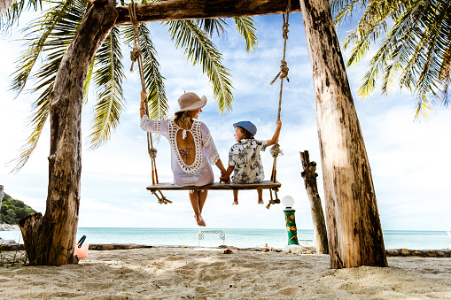 Rear view of carefree mother and son holding hands while swinging at the beach.
