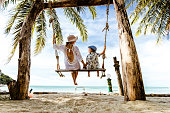 Back view of mother and son enjoying in summer day while swinging at sandy beach in summer day.
