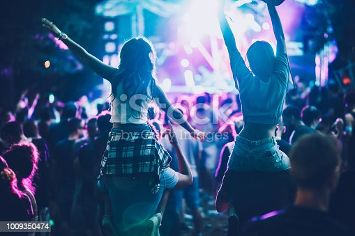 Back view of carefree women having fun while being on man's shoulders during music festival.
