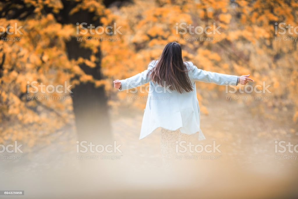 Rear view of carefree woman enjoying in fresh autumn air. stock photo