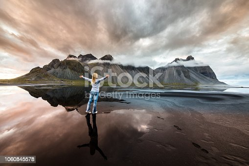 Back view of a woman feeling free at Vestrahorn mountain at Stokksness peninsula, Iceland.