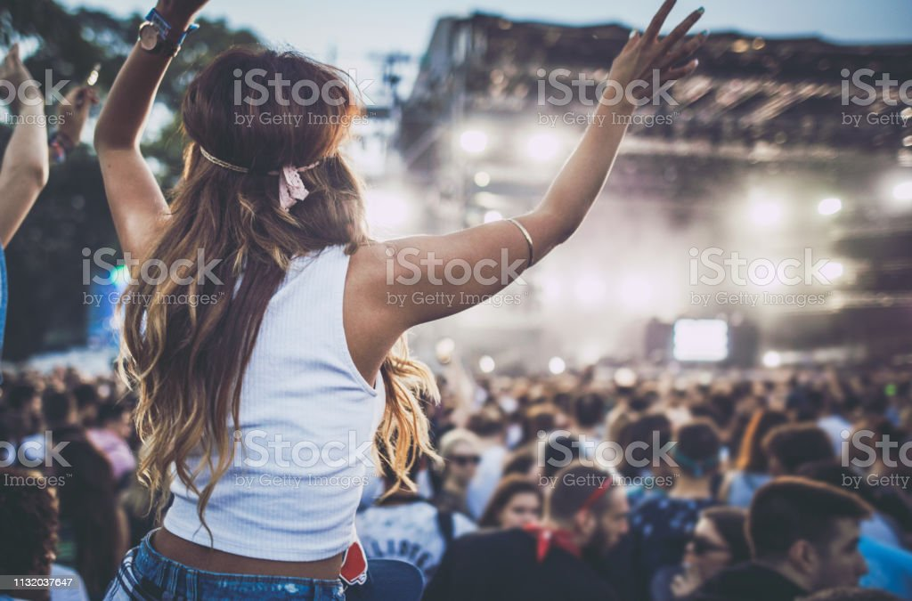 Back view of woman with arms raised having fun at music concert.