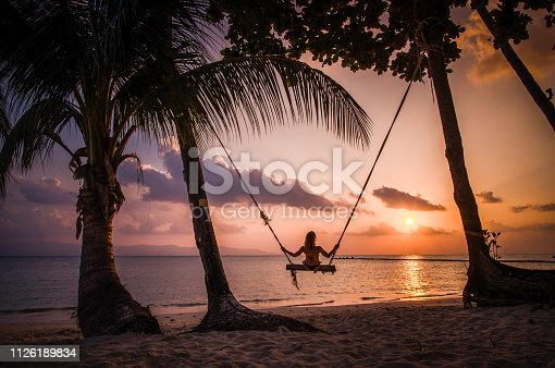 Back view of a woman swinging on the beach during summer vacation at sunset.