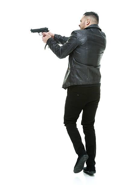 Rear view of casual man aiming with gun stock photo