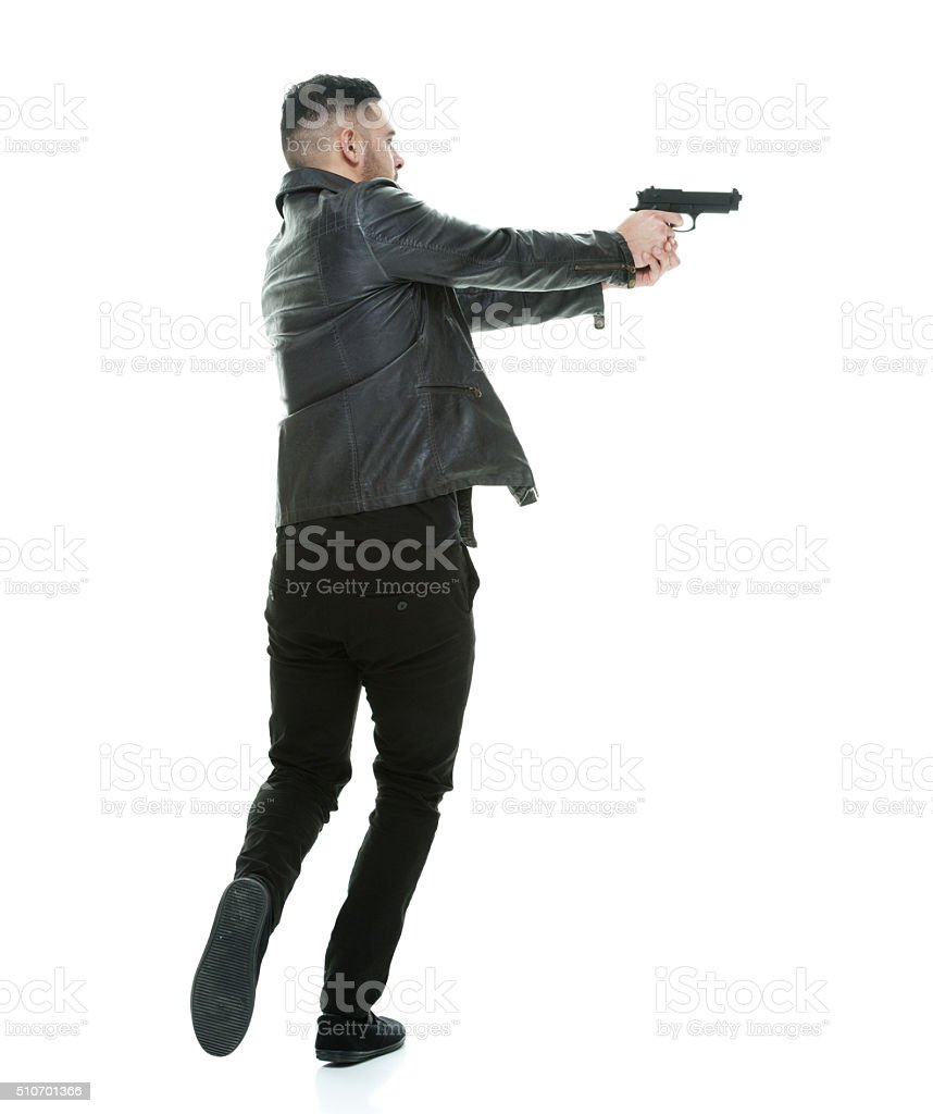 Rear view of casual man in action with handgun stock photo
