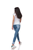 rear view of brunette casual woman walking on white background and looking to side, full length picture