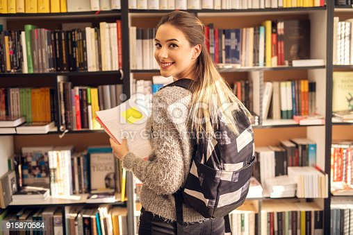 istock Rear view of charming stylish smiling teenage student girl with backpack standing in the sunny school library in front of the bookshelf with notes in hands while looking at the camera. 915870584
