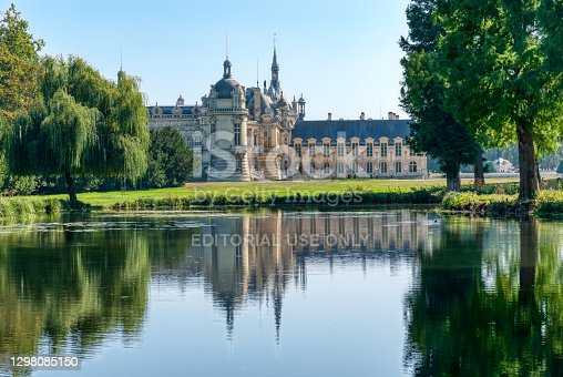 istock Rear view of Chateau de Chantilly with reflection in a pond - France 1298085150