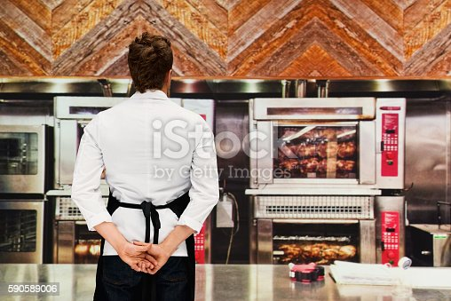 Rear view of chef standing in kitchenhttp://www.twodozendesign.info/i/1.png