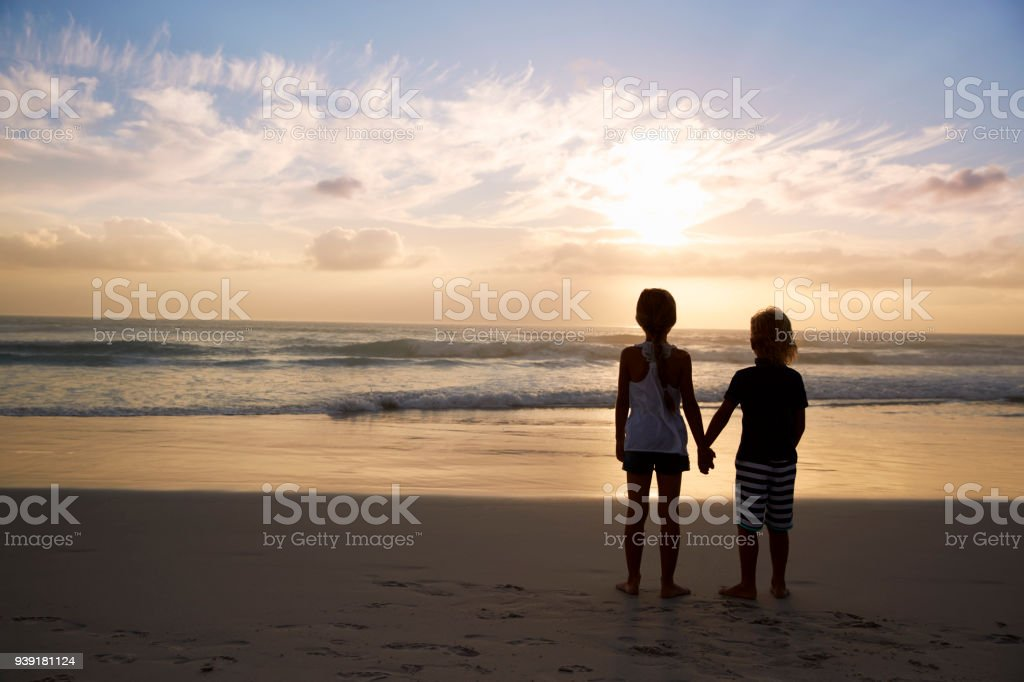 Rear View Of Children Holding Hands Silhouetted On Beach stock photo