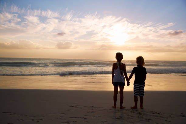 Rear View Of Children Holding Hands Silhouetted On Beach Rear View Of Children Holding Hands Silhouetted On Beach sister stock pictures, royalty-free photos & images