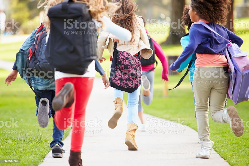 Rear View Of Children Running Along Path In Park stock photo