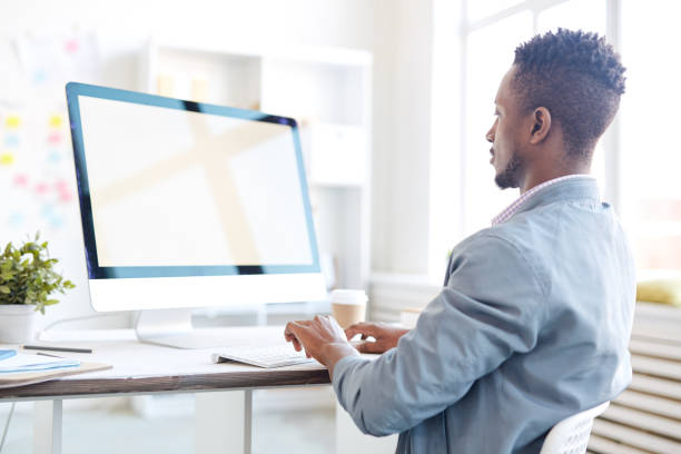Rear view of concentrated busy black male programmer typing on computer keyboard while working on project in modern office stock photo
