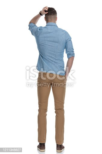 Rear view of confused casual man scratching his head while wearing blue shirt, standing on white studio background