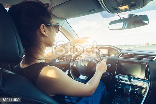 istock rear view of cool girl in sunglasses driving car 852411532