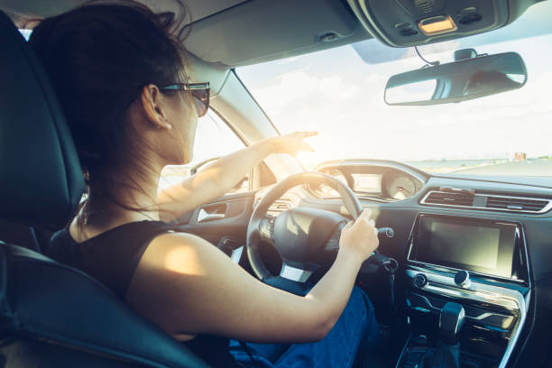 rear view of cool girl in sunglasses driving car - car interior stock photos and pictures